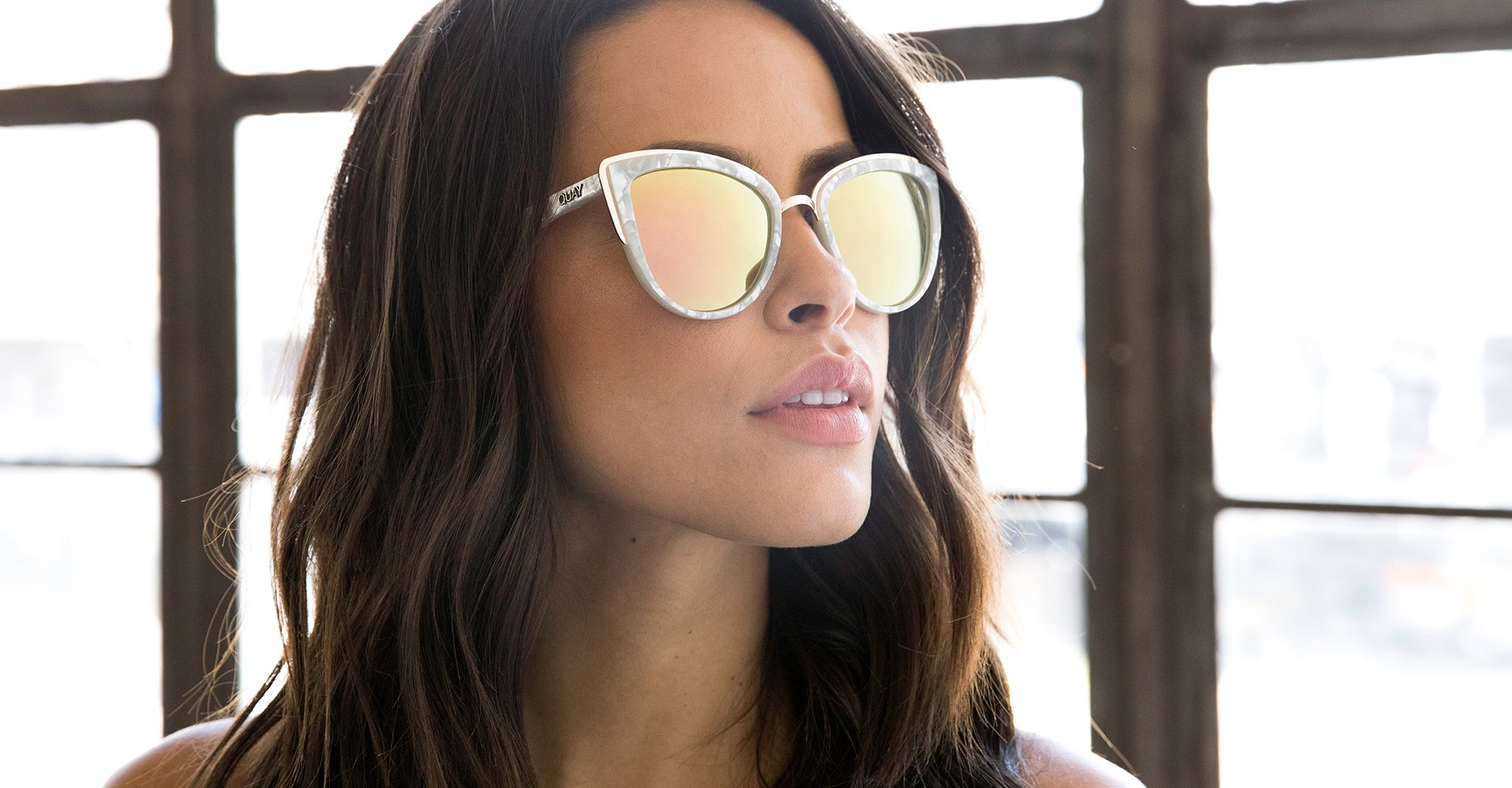 Image of a woman by a window wearing Quay Sunglasses