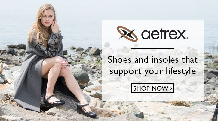 Clickable image of a woman sitting on the beach wearing aetrex sandles