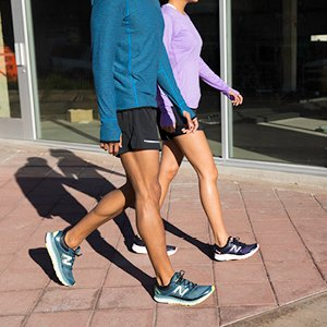 Man and woman wearing New Balance apparel and footwear.