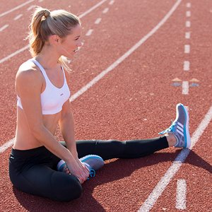 Woman stretching on running track.