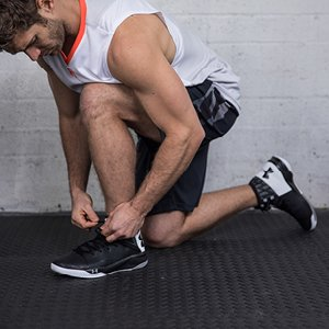 Man tying shoes wearing Under Armour apparel and footwear.