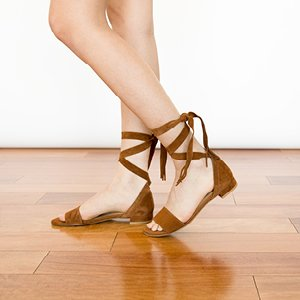 Image of woman wearing Stuart Weitzman tan sandals.