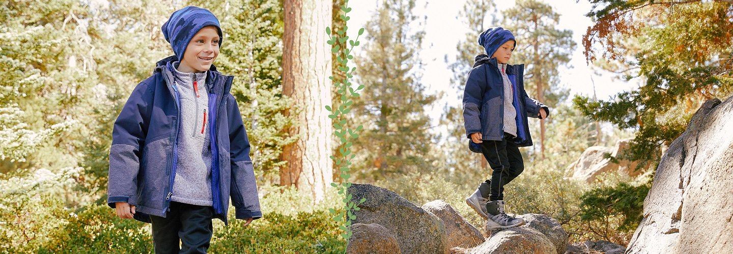 image of boy playing in forest wearing outerwear. image links to selection of boys The North Face outerwear for fall and winter.