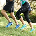 Image of a man and woman running outside in Merrell shoes