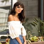 Women wearing a white off the shoulder top and blue jeans