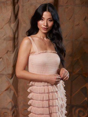 Woman wearing ruffled peach dress.