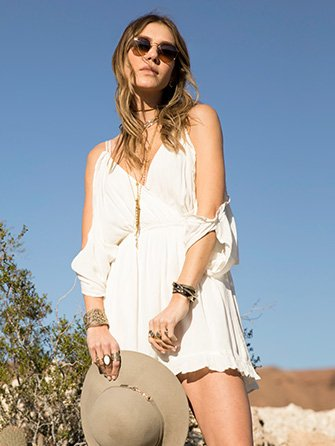 Festival look. Woman wearing white dress and brown boots.