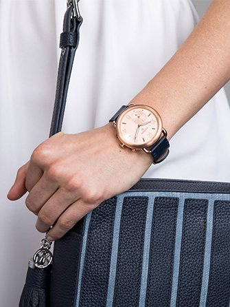 White and Stripes. Close up of fossil watch and blue and light blue striped handbag.
