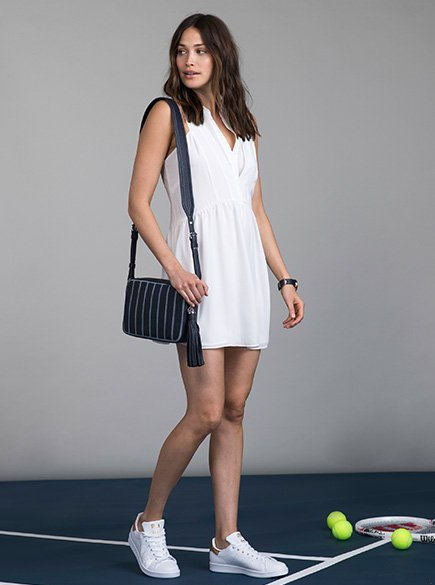White and Stripes. Woman wearing tennis inspired white dress and white sneakers.