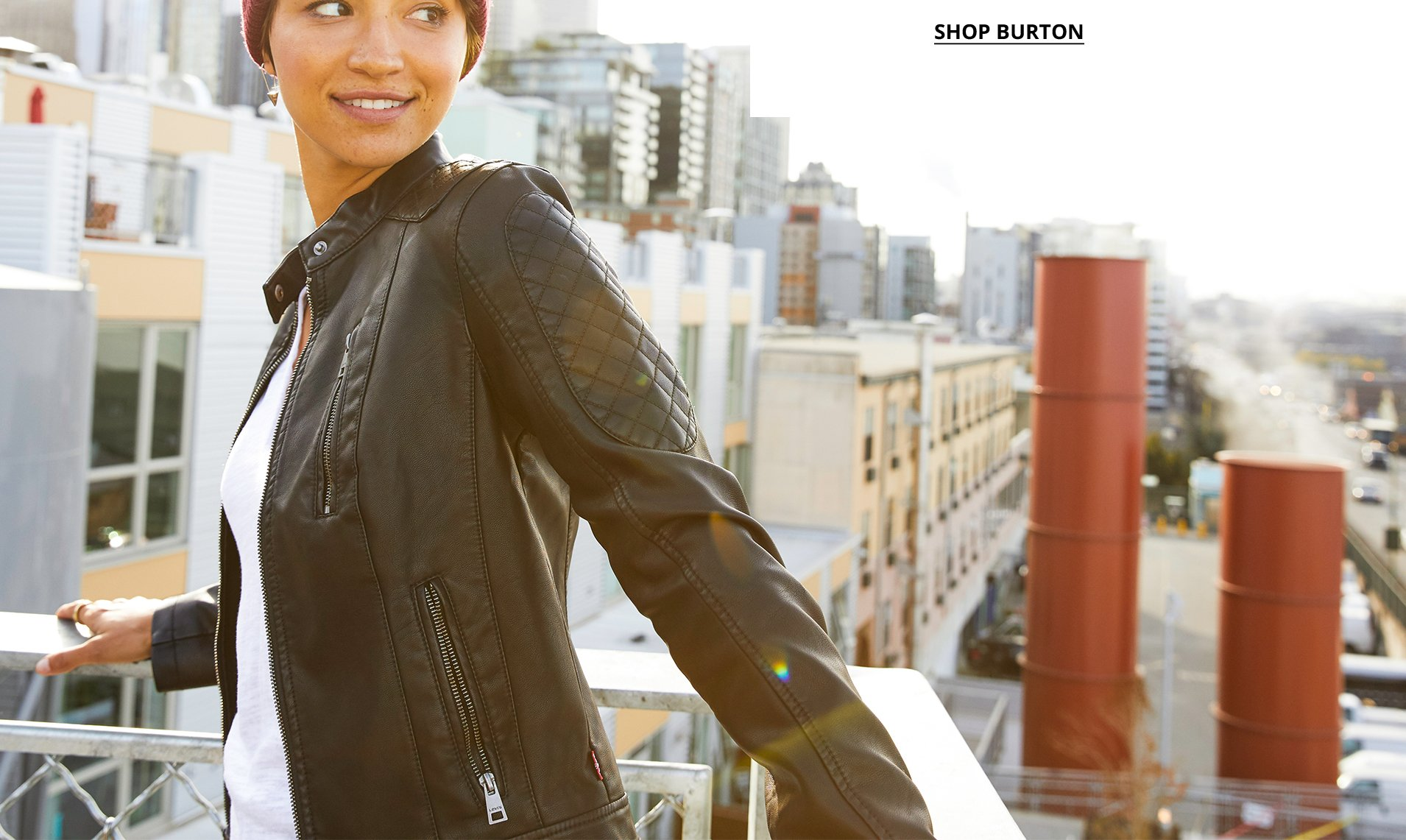 Image of a woman wearing a red beanie and a black leather jacket in front of a city scape.