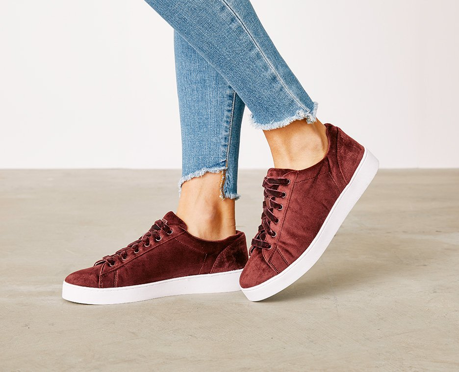 Image of  a women in burgundy velvet sneakers