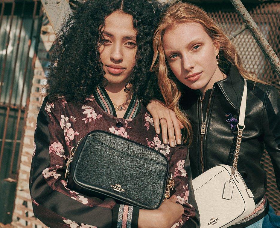Image of two women wearing Coach handbags.