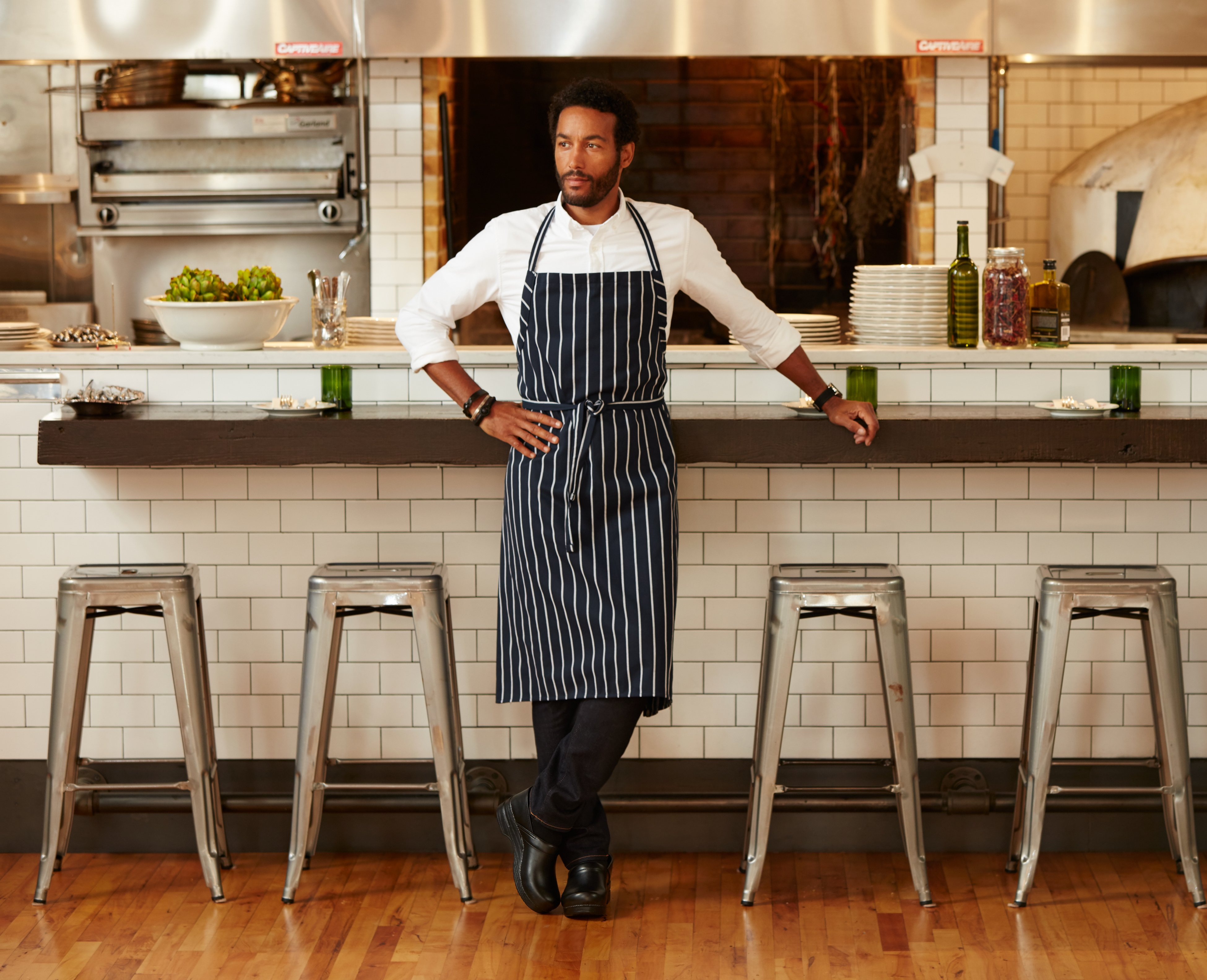 Clickable image of a cook in a restaurant wearing Dansko Clogs