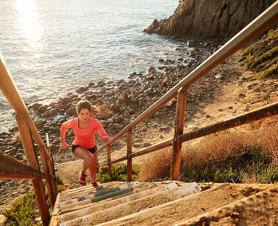 Image of a woman running up stairs wearing Merrell shoes.