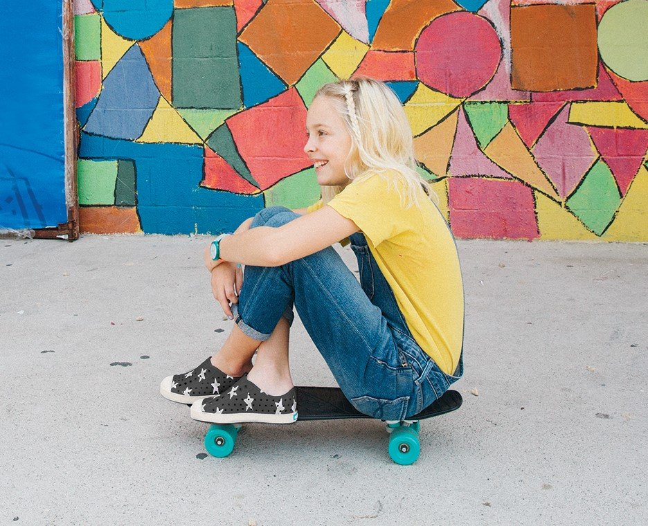 Image of a little girl sitting on a skate board wearing Native Shoes