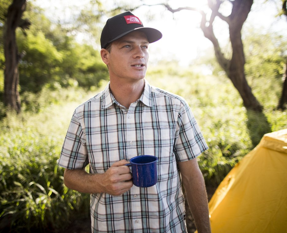 Image of a man wearing a plaid The North Face shirt.