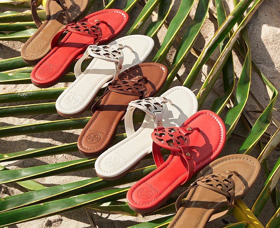 Image of Tory Burch sandals on a palm frond.