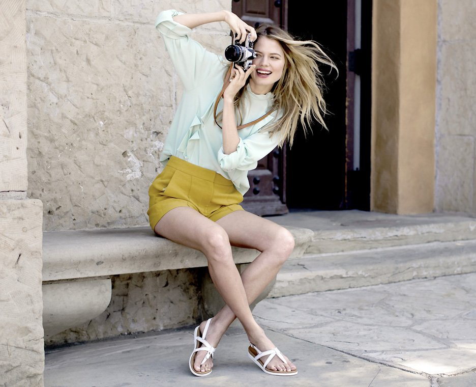 Clickable image of a woman sitting down taking a picture with a camera wearing Vionic Sandals.