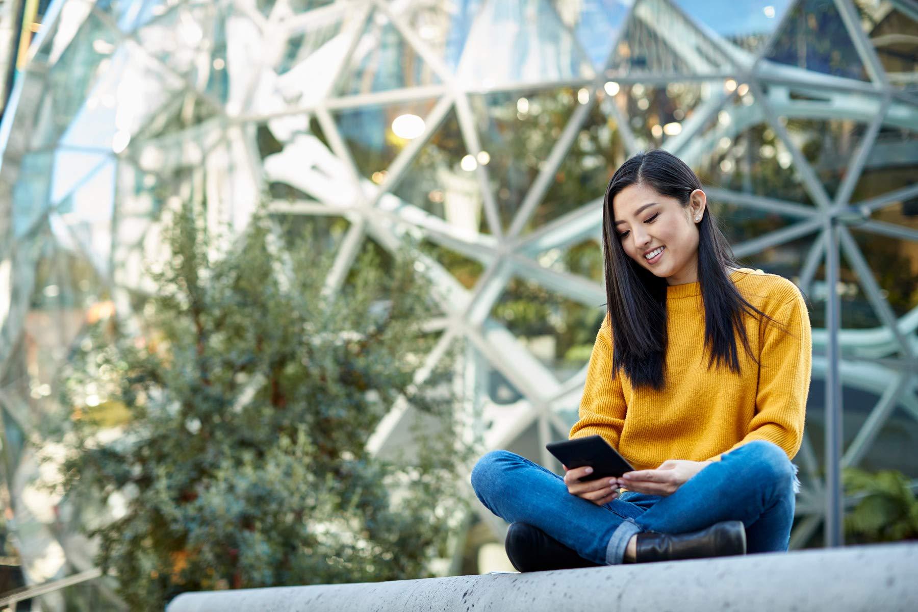 Mujer joven sentada junto a las esferas de Amazon y mirando una tableta