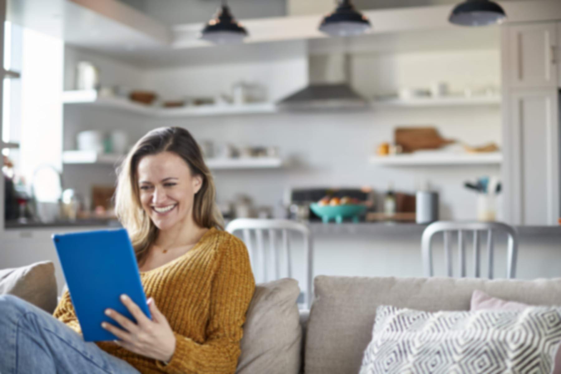 Una mujer en un sofá ríe mientras usa su Fire tablet de Amazon