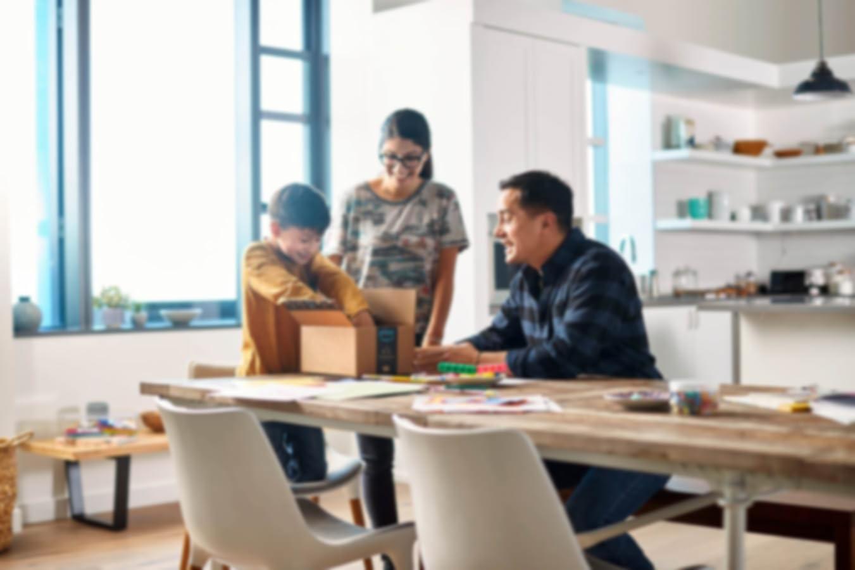 Famille ouvrant un paquet Amazon à la table de la cuisine