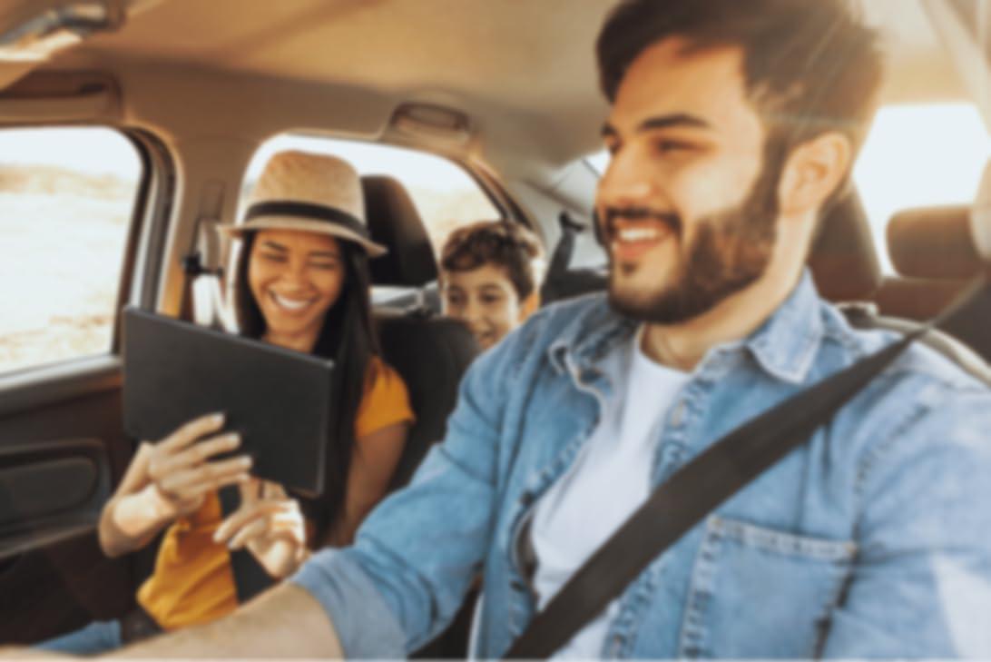 Familie fährt gemeinsam im Auto, Beifahrer schauen auf ein Tablet-Gerät