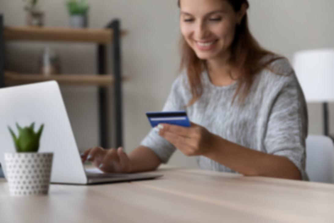 办公桌前坐着的一位女士正在将信用卡信息输入电脑中