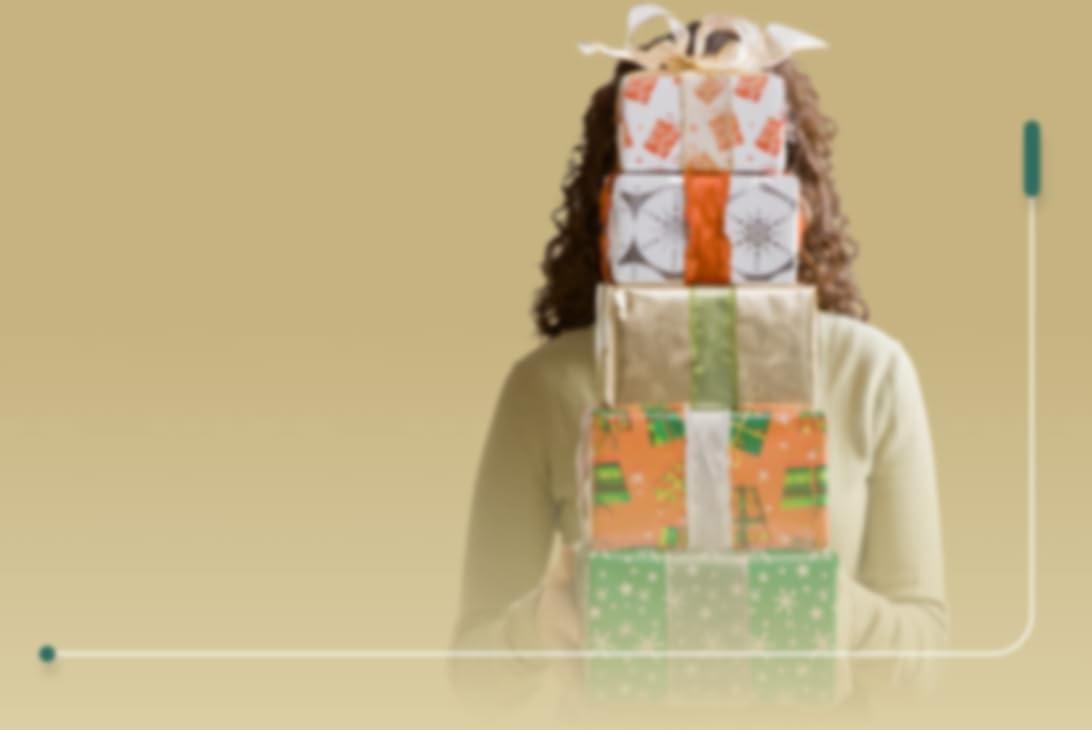 persoon met golvend haar die een stapel cadeautjes vasthoudt, verpakt in verschillende soorten cadeaupapier en met een grote strik eromheen. De cadeautjes vormen een stapel in de vorm van een kerstboom, waarachter het gezicht van de persoon schuilgaat.