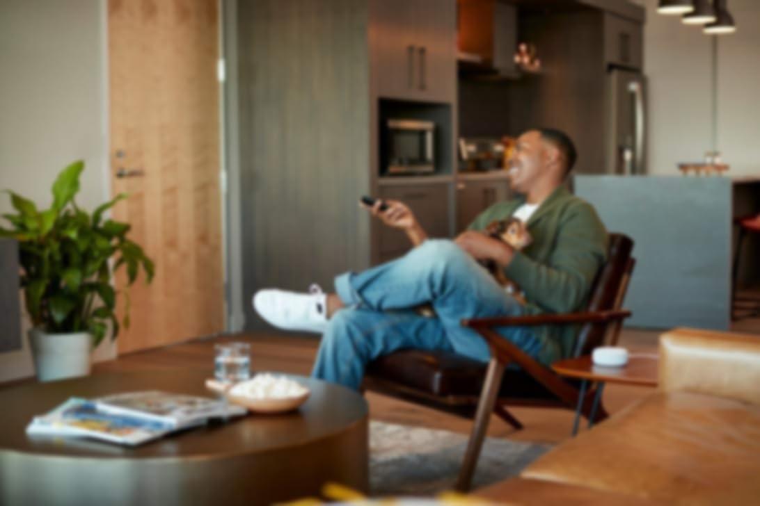 男人把狗抱在腿上,用遥控器对着电视