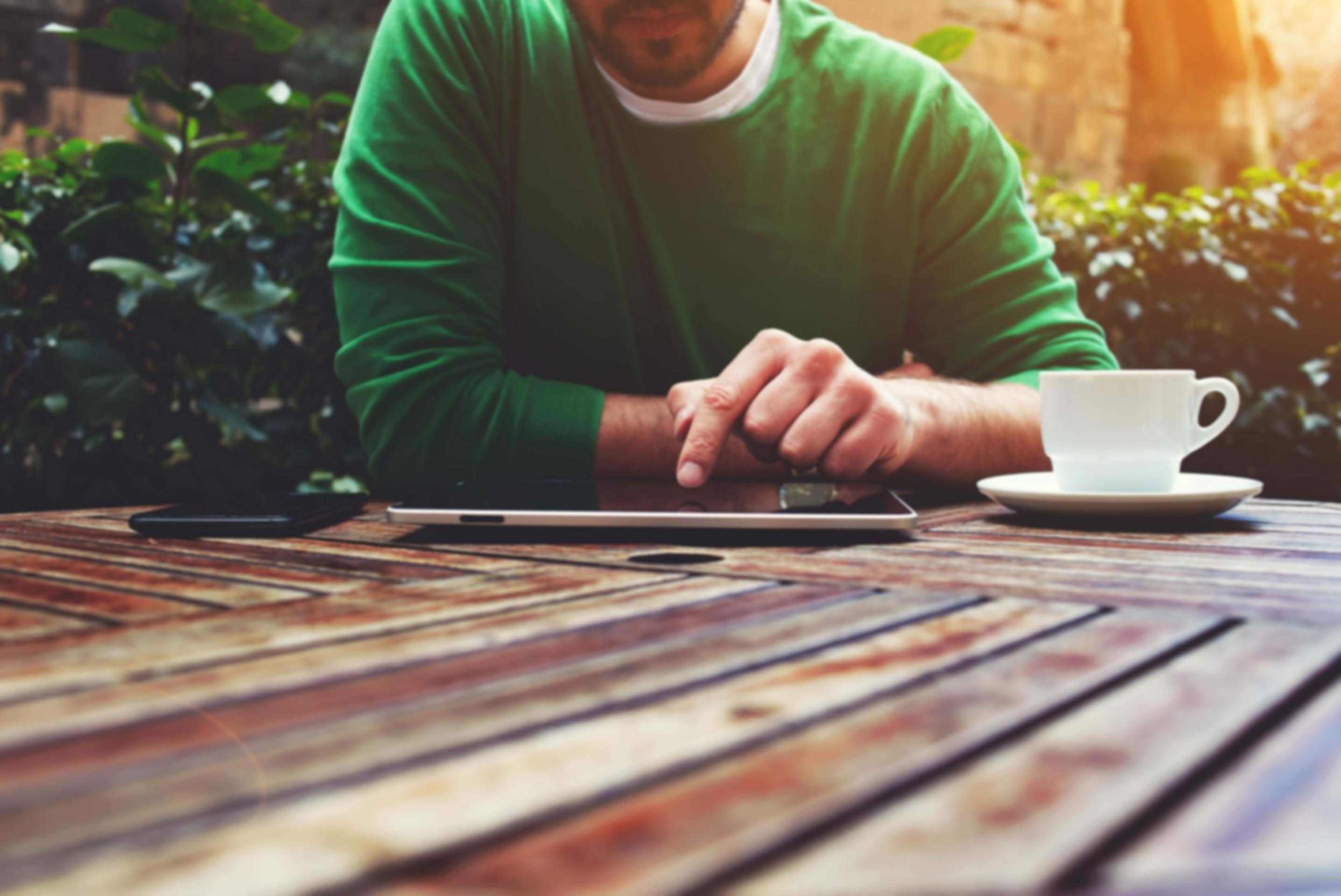 男子坐在室外的桌子旁使用平板电脑工作。