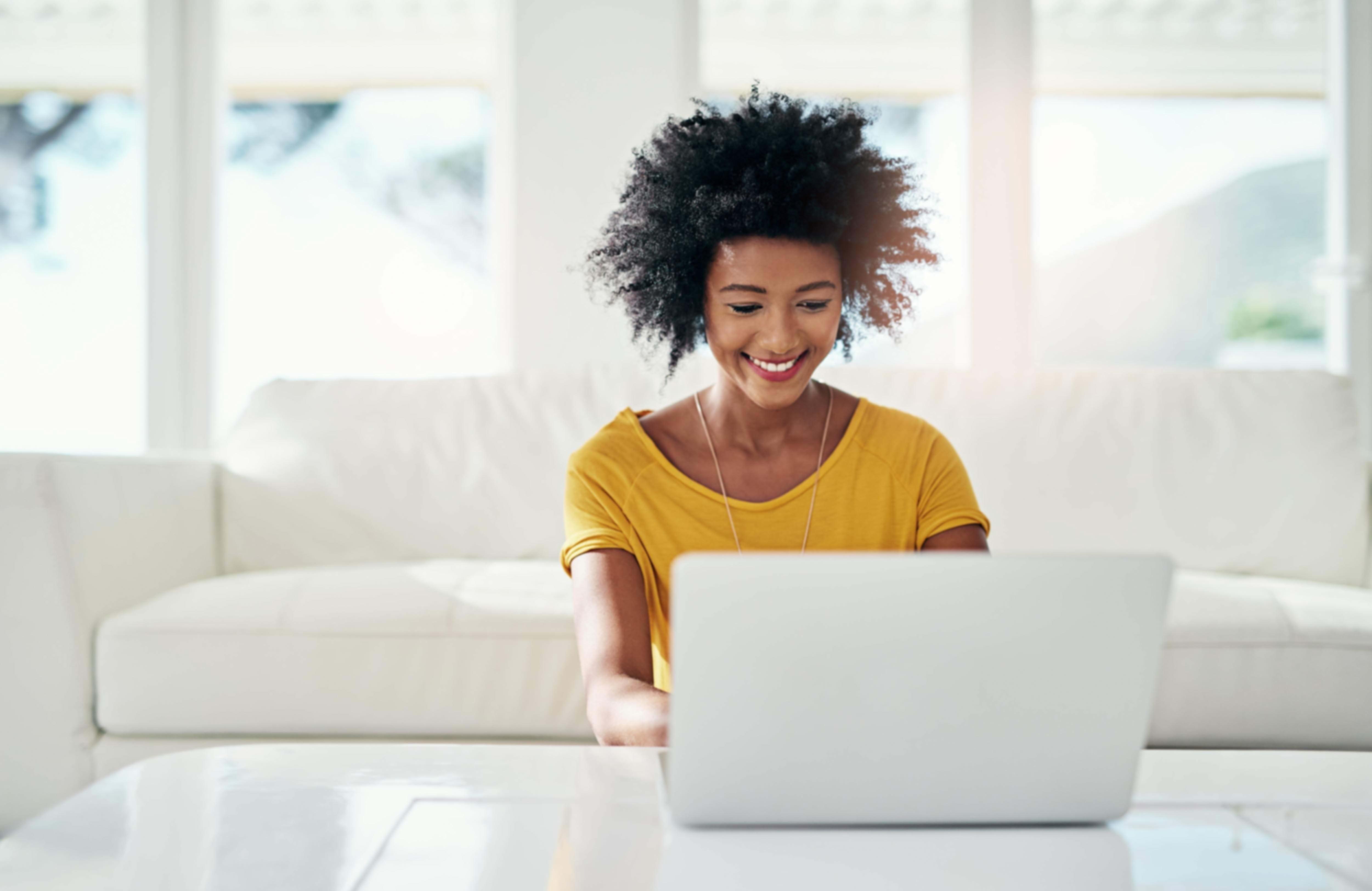 Woman, smiling, looking at laptop screen.