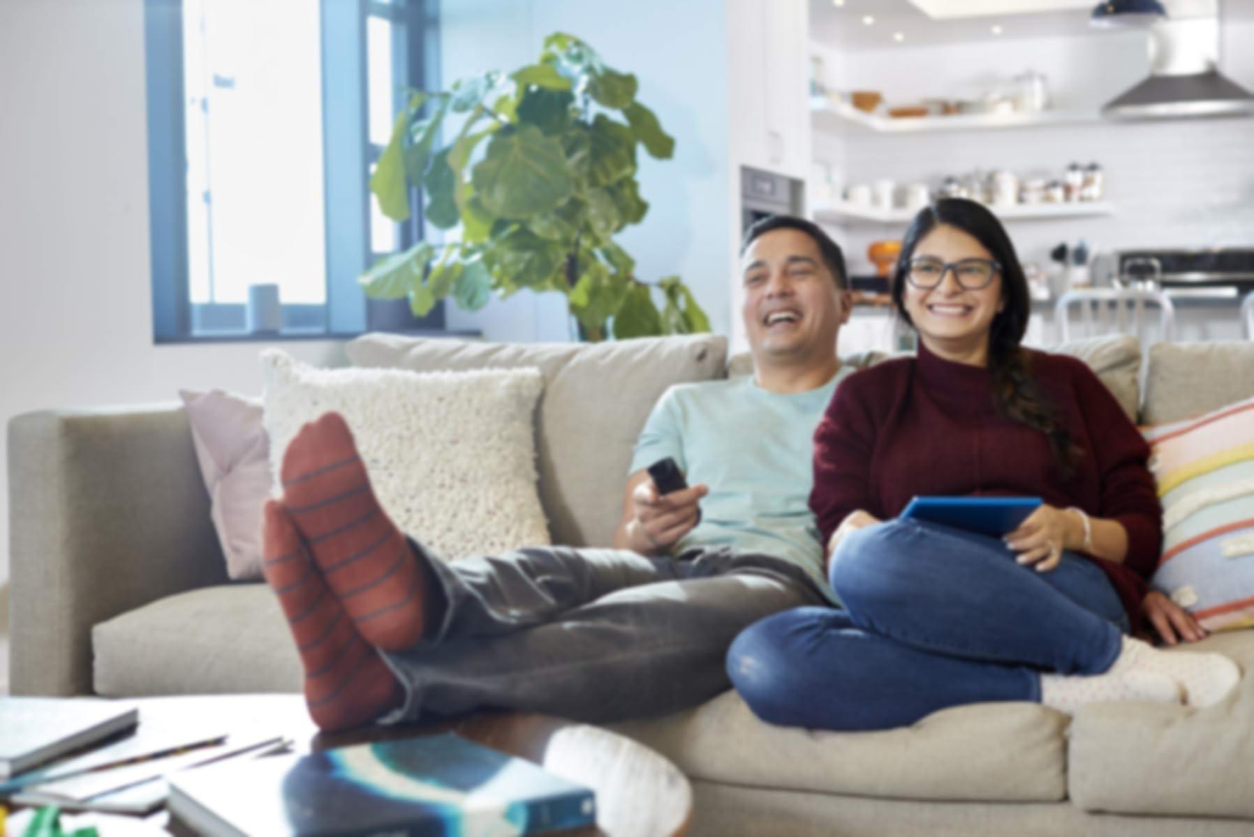 Couple assis sur un canapé en train de regarder la télé.