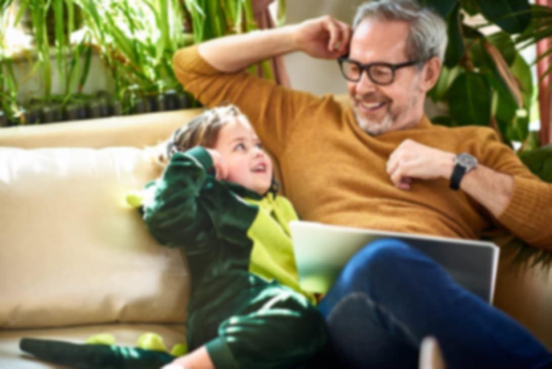 一位在使用平板电脑的父亲与一个年幼的孩子坐在沙发上