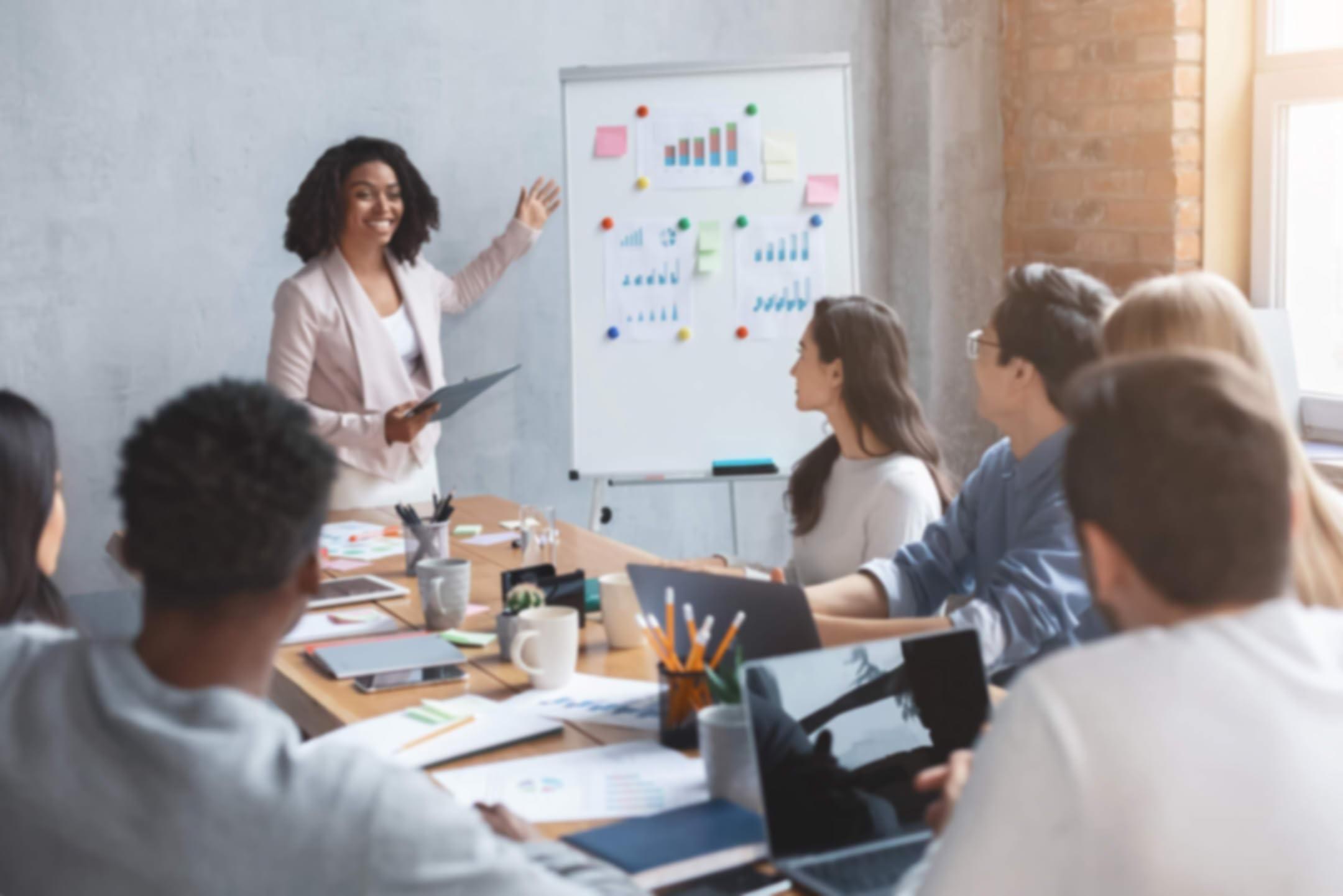 站在白板旁边的女子向坐在会议桌旁的人们讲话。