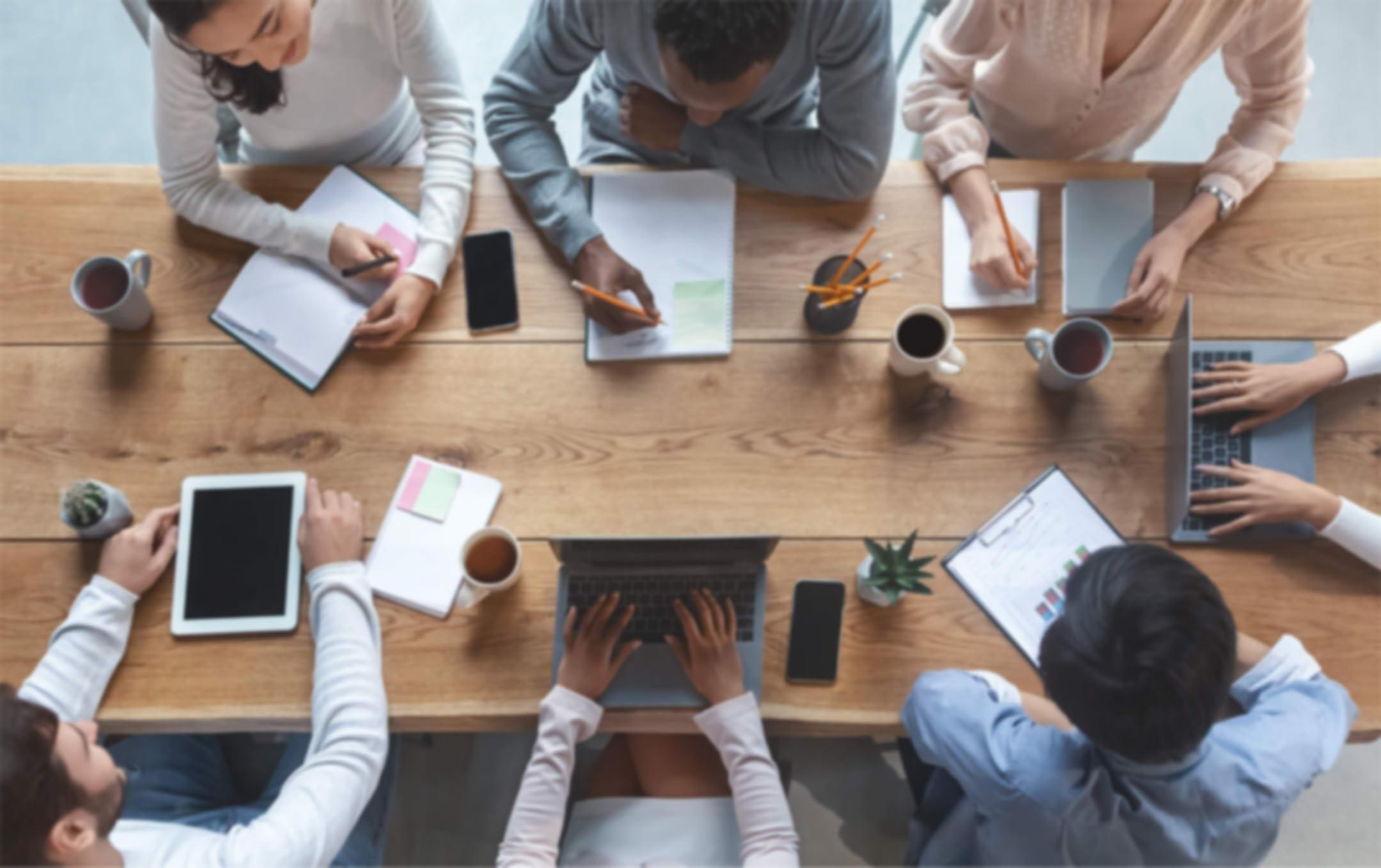 Vue à vol d'oiseau de personnes assises autour d'une table lors d'une réunion, prenant des notes et travaillant sur leurs ordinateurs portables et tablettes.