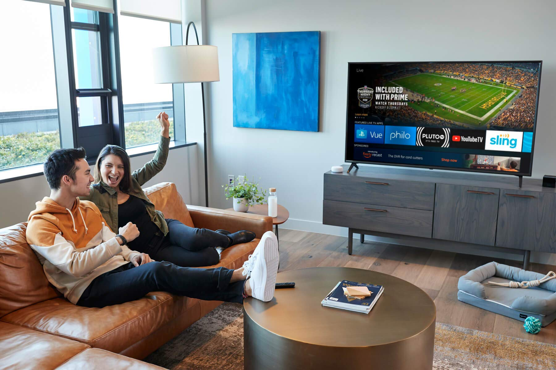 Man and woman sitting on a couch in a living room cheering in front of a TV.