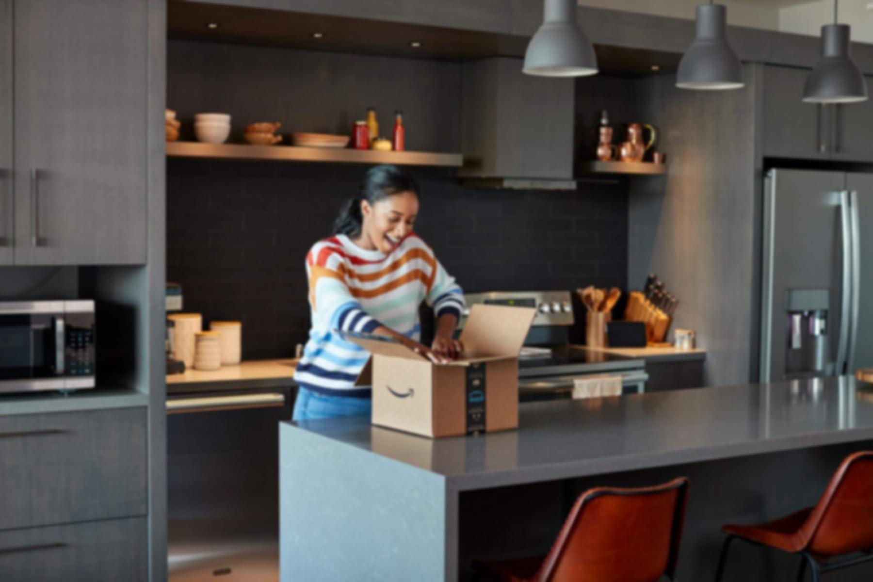 Donna che apre un pacco Amazon in piedi in una cucina.