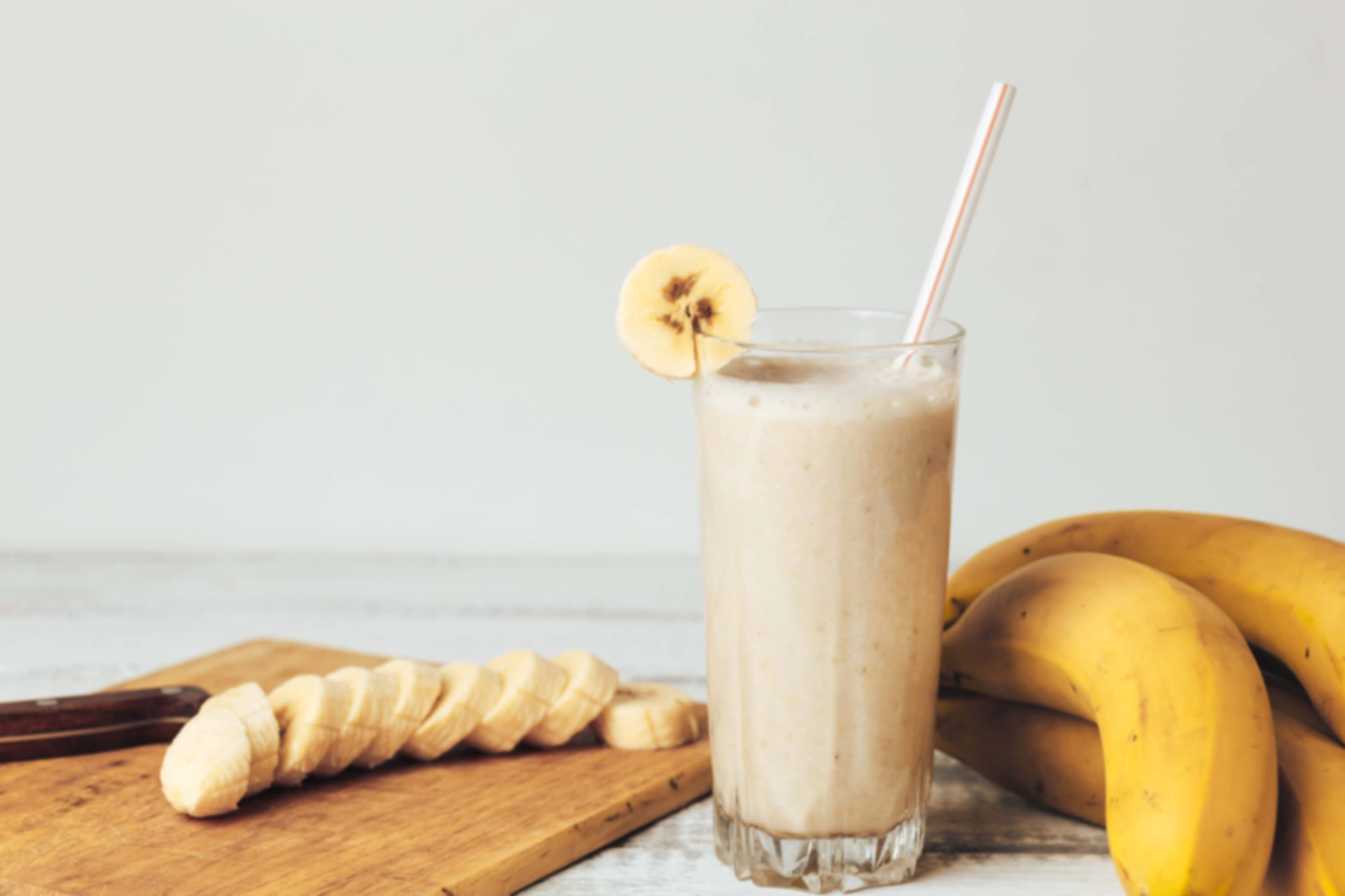 Smoothie in a glass with a straw. Sliced and whole banana surrounding.