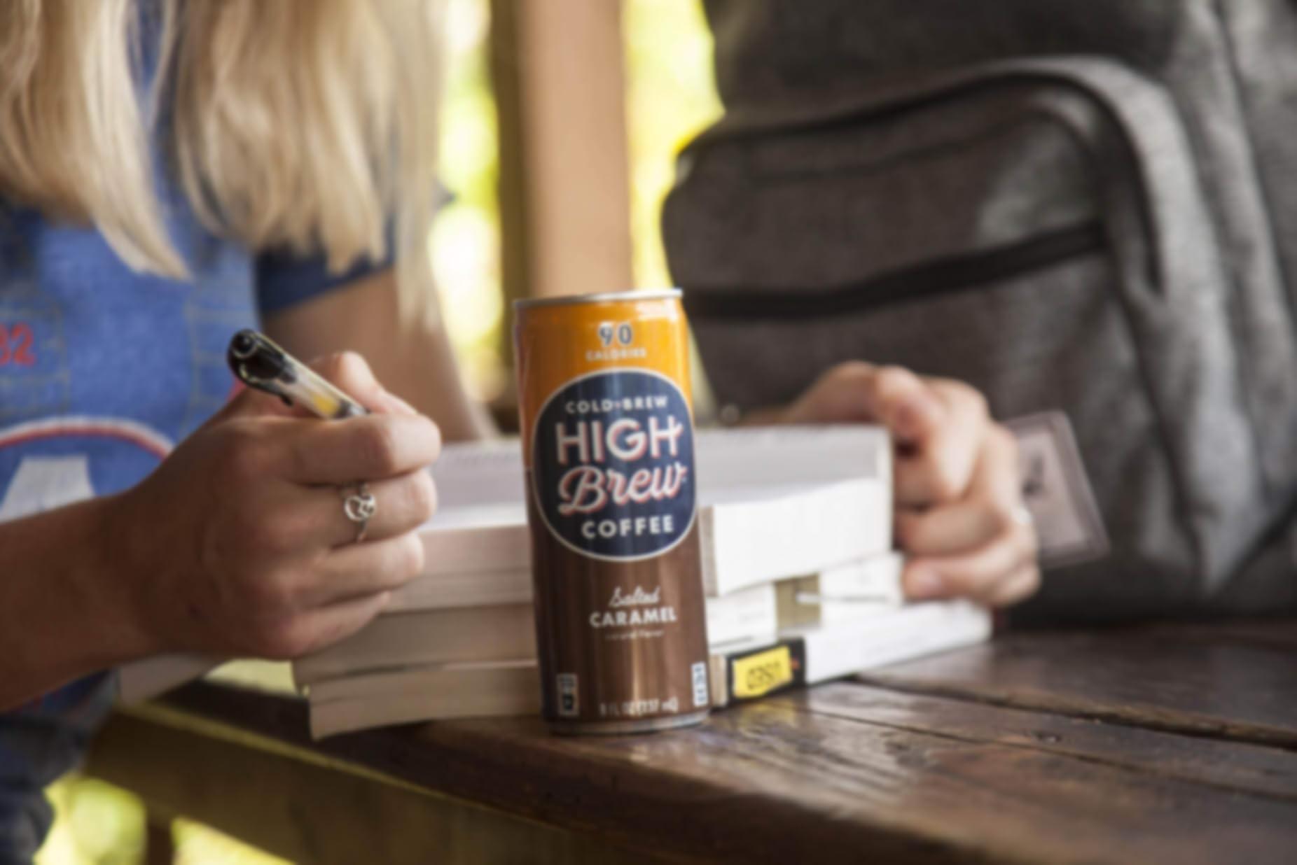 Studente che studia con una lattina di High Brew Coffee vicino ai libri.