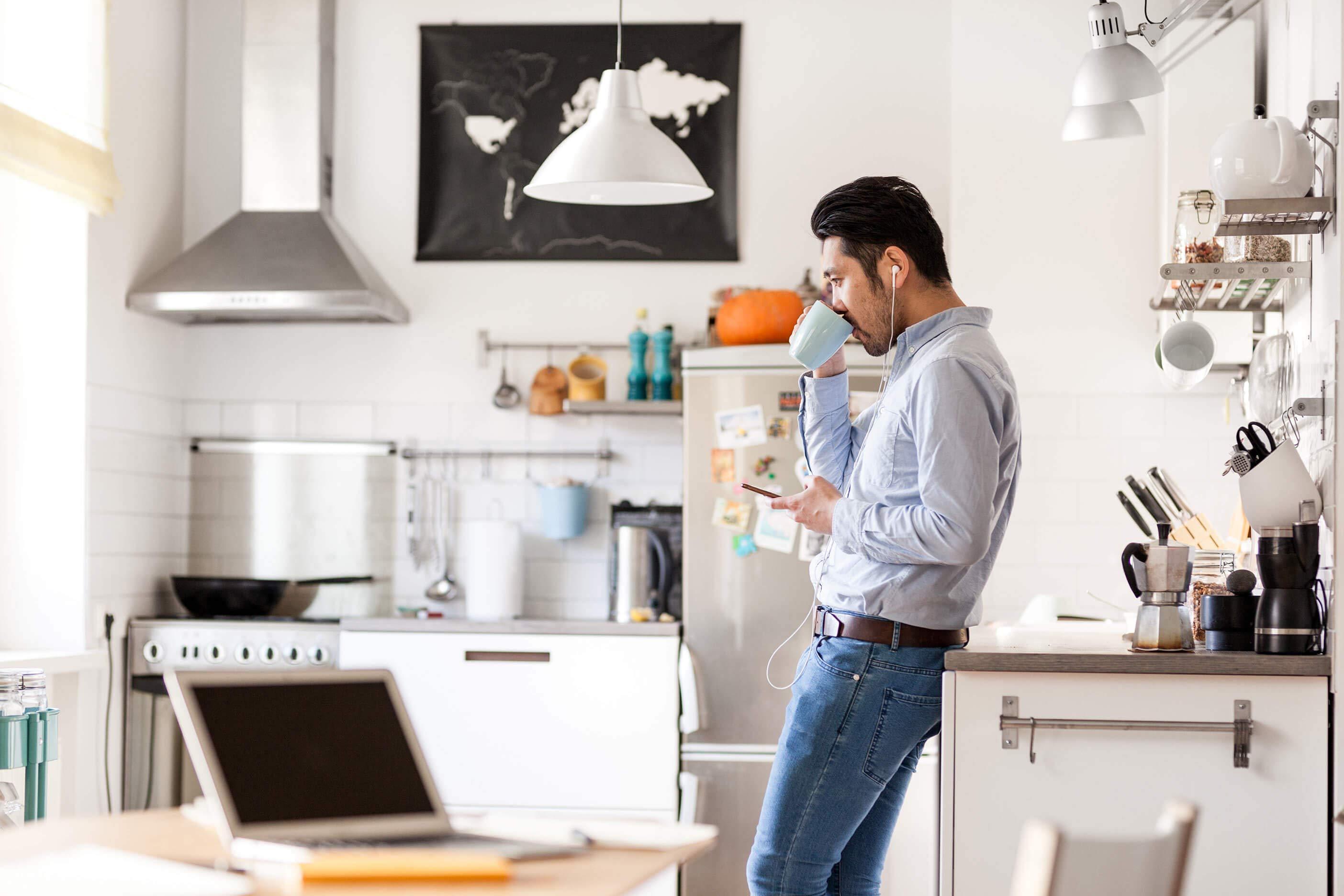 Jeune homme qui boit du café dans une cuisine en écoutant dans ses écouteurs connectés à son téléphone. Un ordinateur portable est présenté sur la table à l'avant-plan.