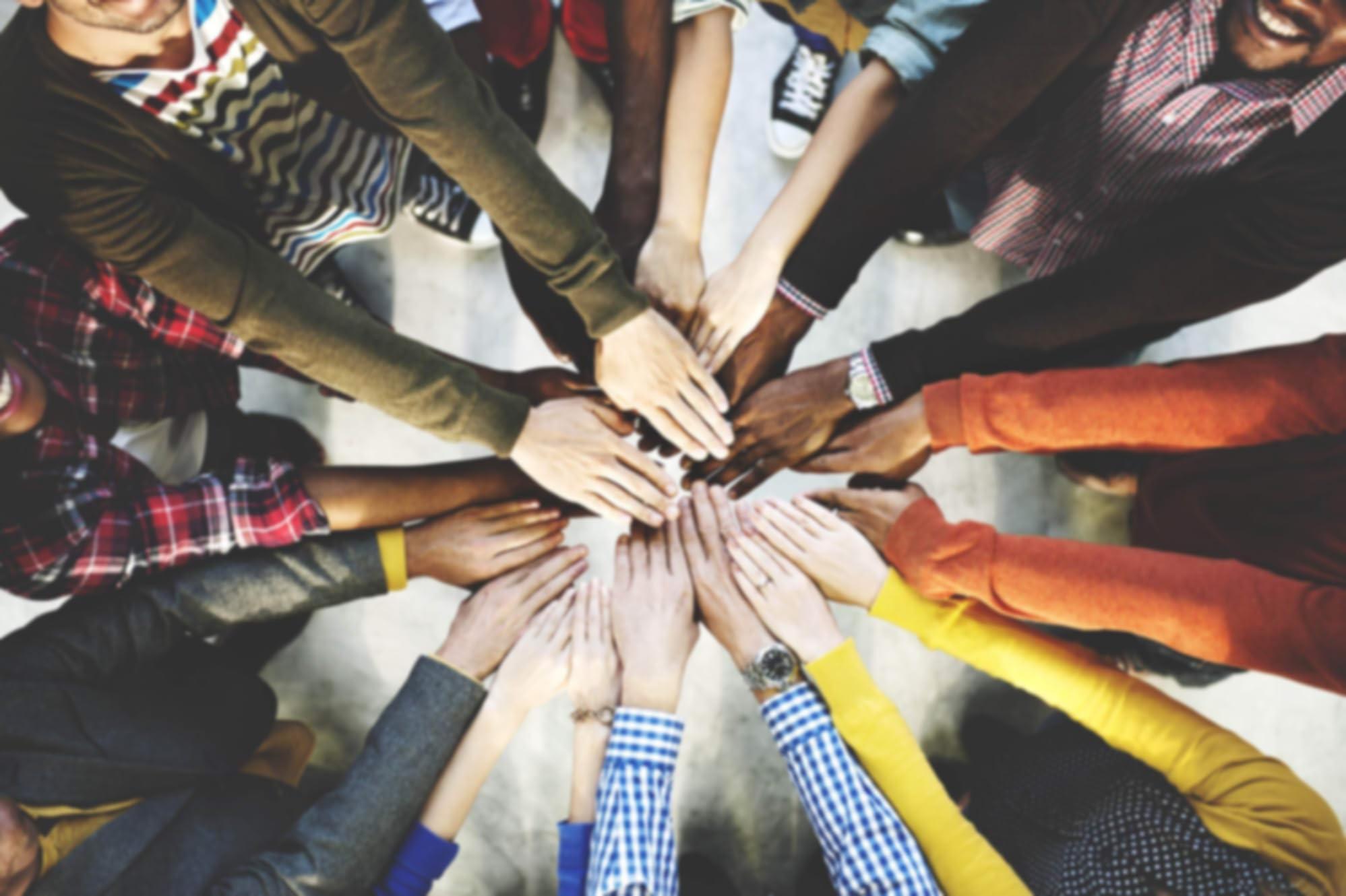 Varias personas añadiendo sus manos en un círculo.