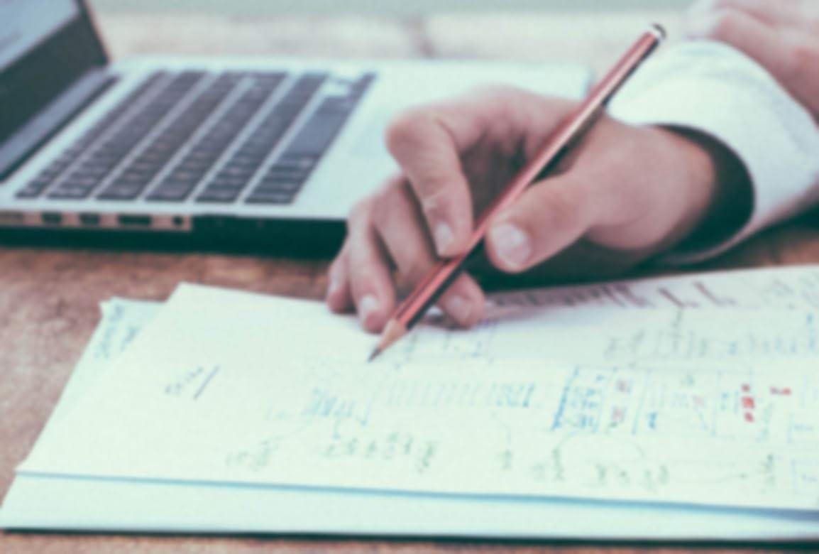 Personne qui rédige des notes sur un bout de papier, avec un ordinateur portatif en arrière-plan.