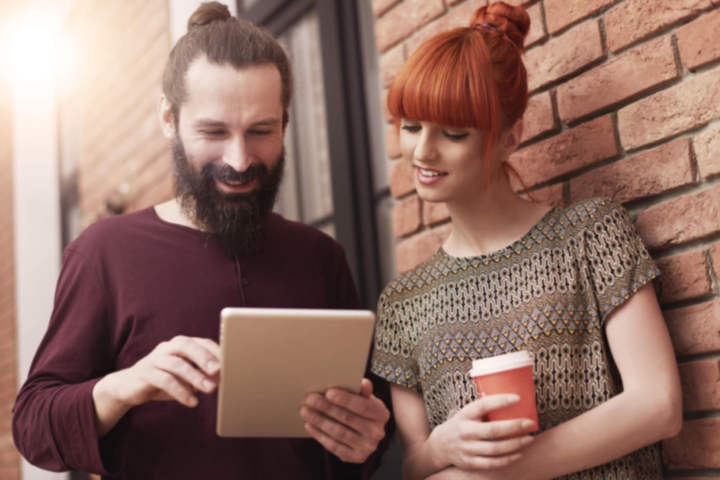 Mann und Frau, die auf ein Tablet schauen.
