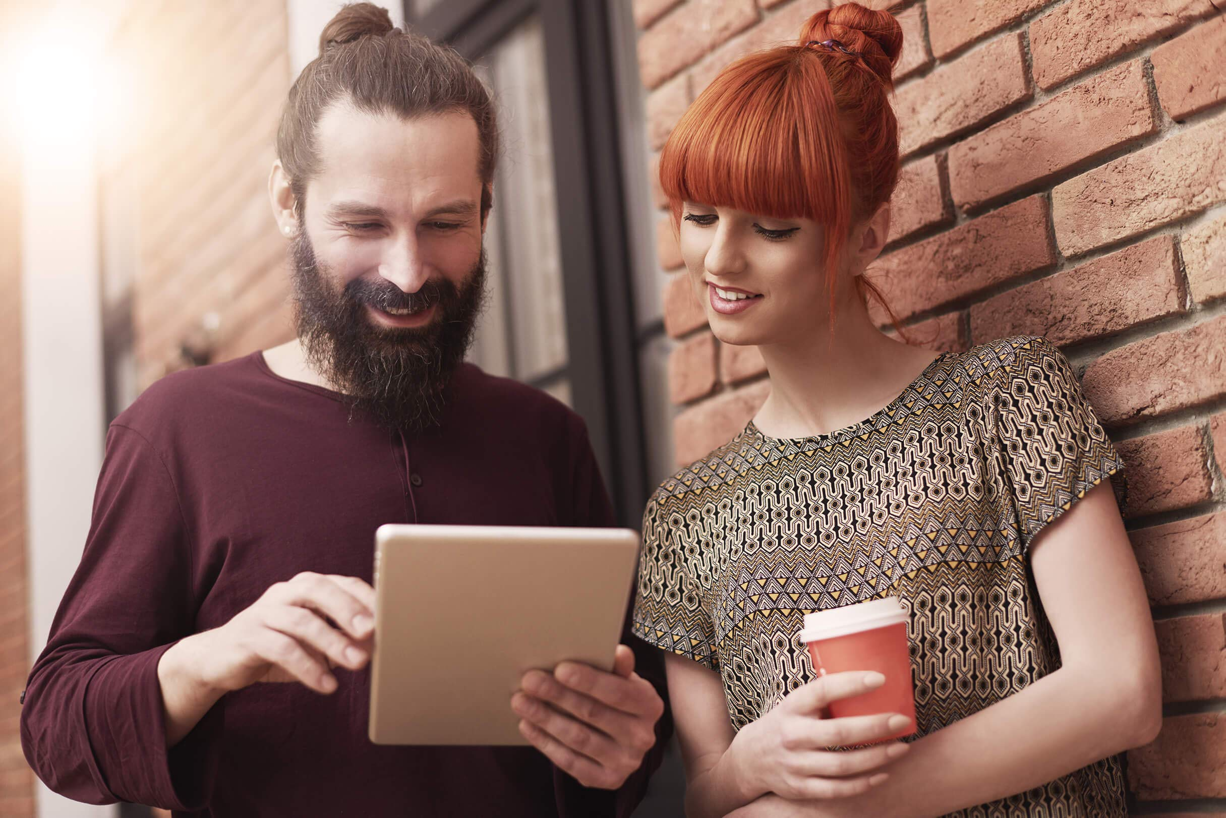 Man and woman looking at a tablet.