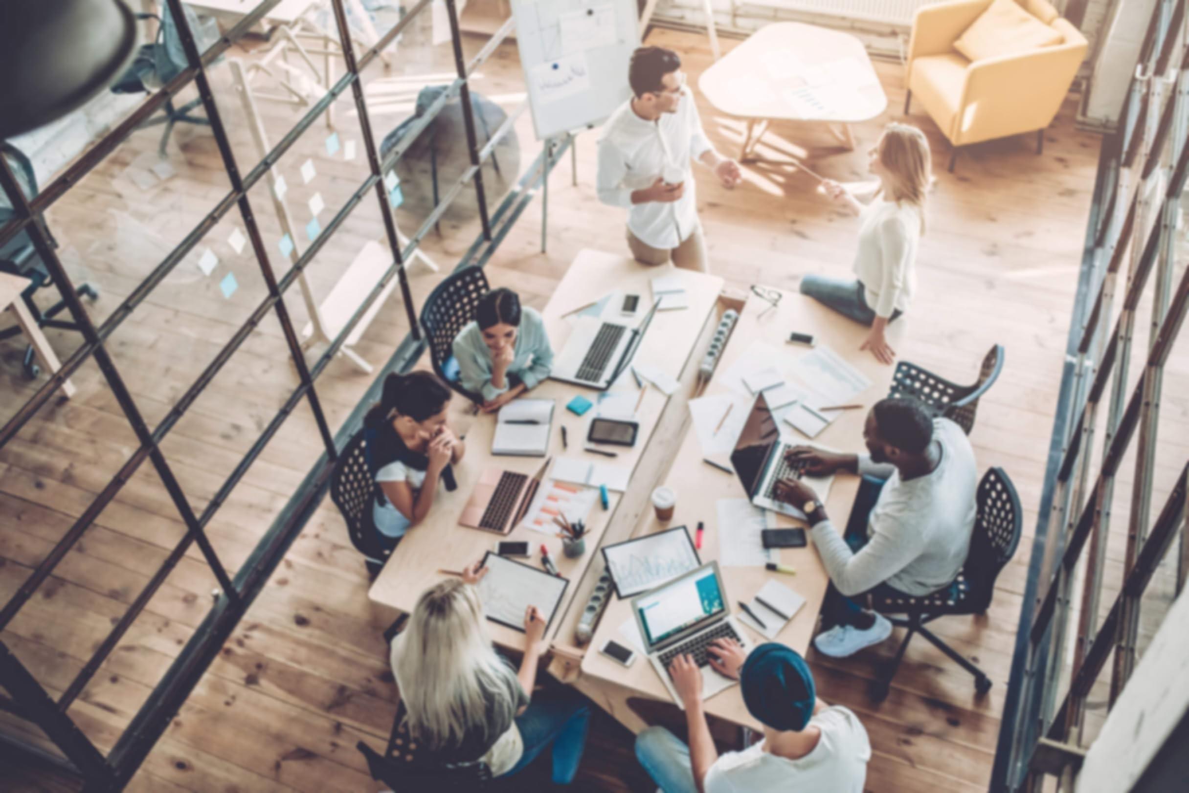 Cinco pessoas em um escritório sentadas em uma mesa com laptops colaborando no trabalho. Duas pessoas de pé perto da mesa conversando.