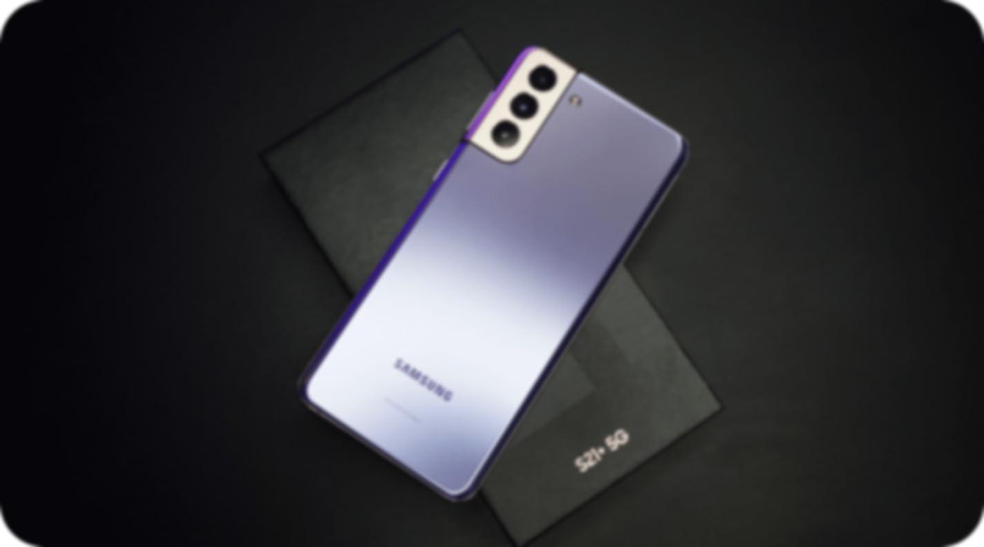 a purple samsung phone lying on top of a black Samsung box