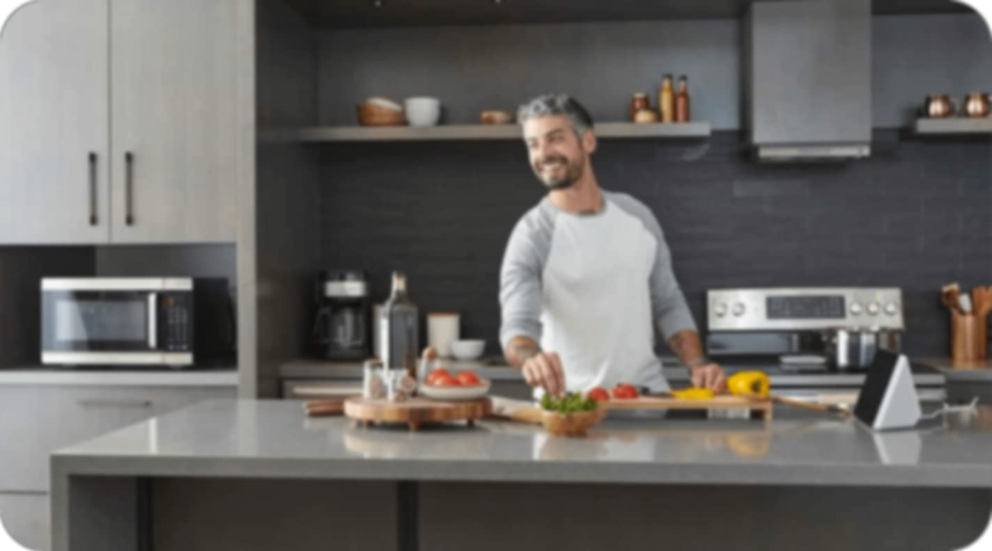 a person cooking in the kitchen with all their ingredients laid out on the table and smiling while looking to the side