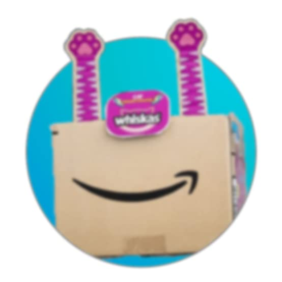 whiskas cat food ad on an amazon shipping box. there are purple cardboard paws at the top and a whiskas logo in the middle