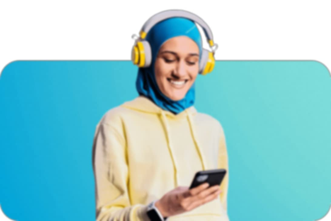 person with blue hijab tucked into a yellow pullover hoodie looking down at their phone with headphones over their ears and hijab