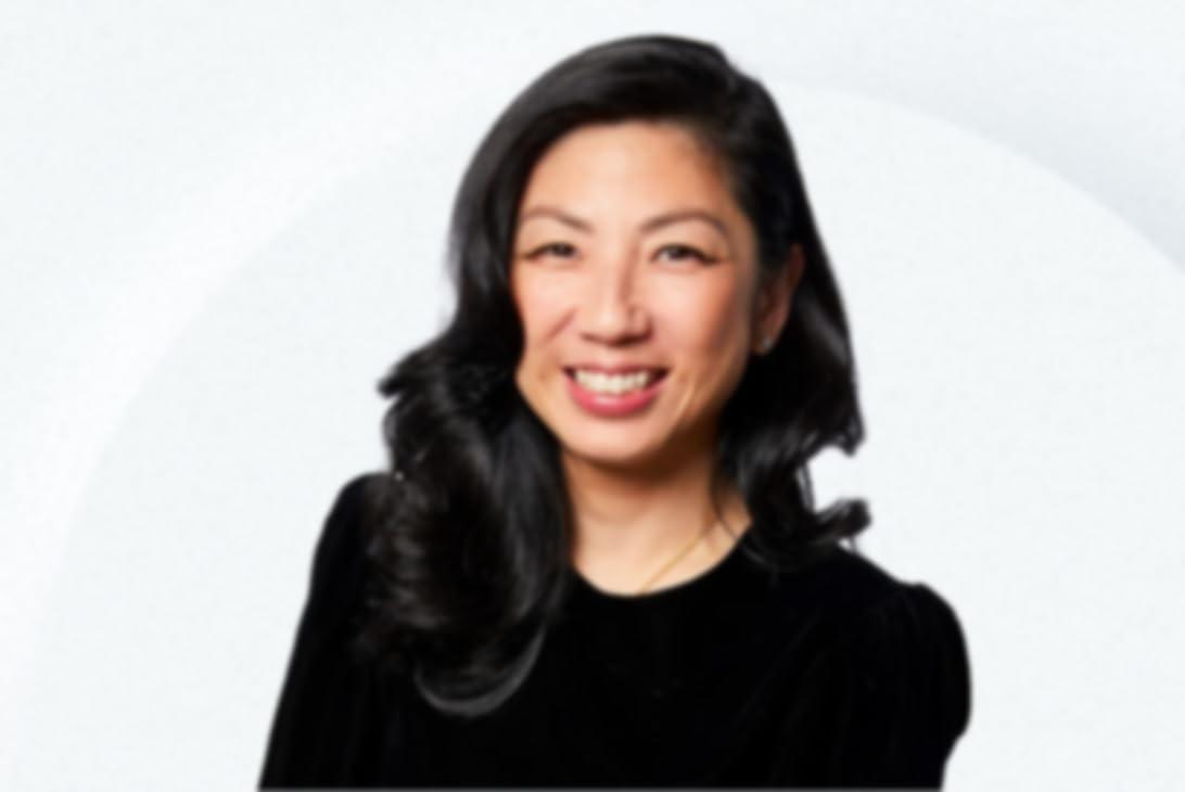 Lachende Helen Lin met een zwart shirt en een haarlok aan de voorkant van haar gezicht